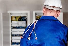 Elektriker mit Helm und blauem Anzug vor einem Stromkasten in der Rückenansicht