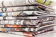 Stapel Zeitungen symbolisiert die Dämm-Kritik und die Dämm-Vorurteile in den Medien.