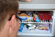 Geöffneter voller Kühlschrank mit Kopf davor.