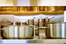 silberne Töpfe und Pfannen auf Küchenanrichte